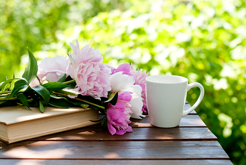 mug on table with pink and purle flowers on a book