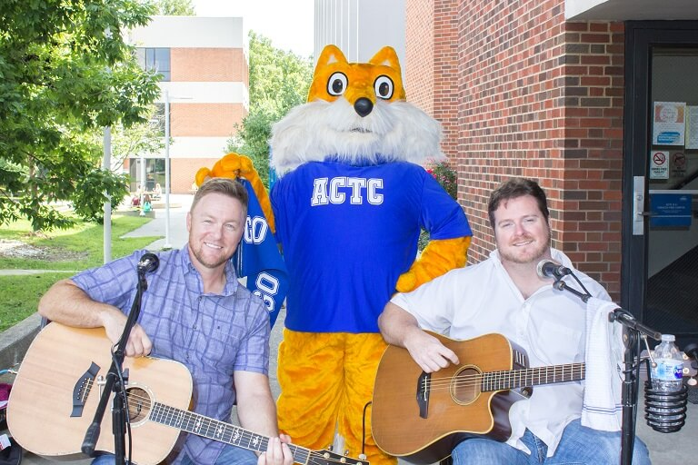 The pathfinder mascot with two musicians outside of the College Drive Campus