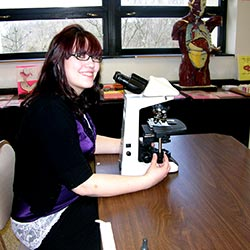 Jessica Cantrell sits at a desk with a microscope