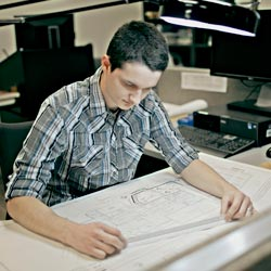 Matthew Adams sits at a drafting table over a architectural diagram
