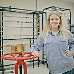 Rebecca Stepp leans against a pipe valve and smiles at the camera