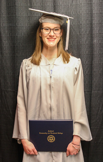 ACTC Grace Browning holds her diploma while dressed in cap and gown