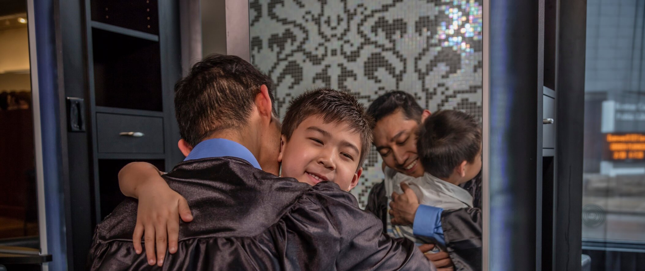 father in graduation robe hugging son
