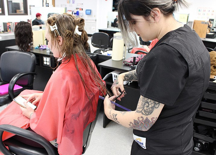 Cosmetology student cutting a customer's hair