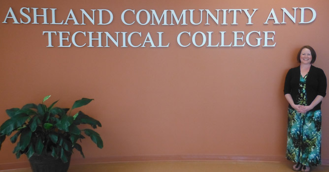 Student Support Services Director and advisor, Megan Horne stands in front of the ACTC logo in the foyer on the Technology Drive Campus.