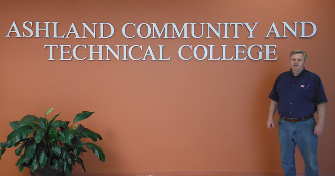 Associate Professor and Advisor Danny Pancake stands in front of the ACTC logo in the foyer on the Technology Drive Campus.