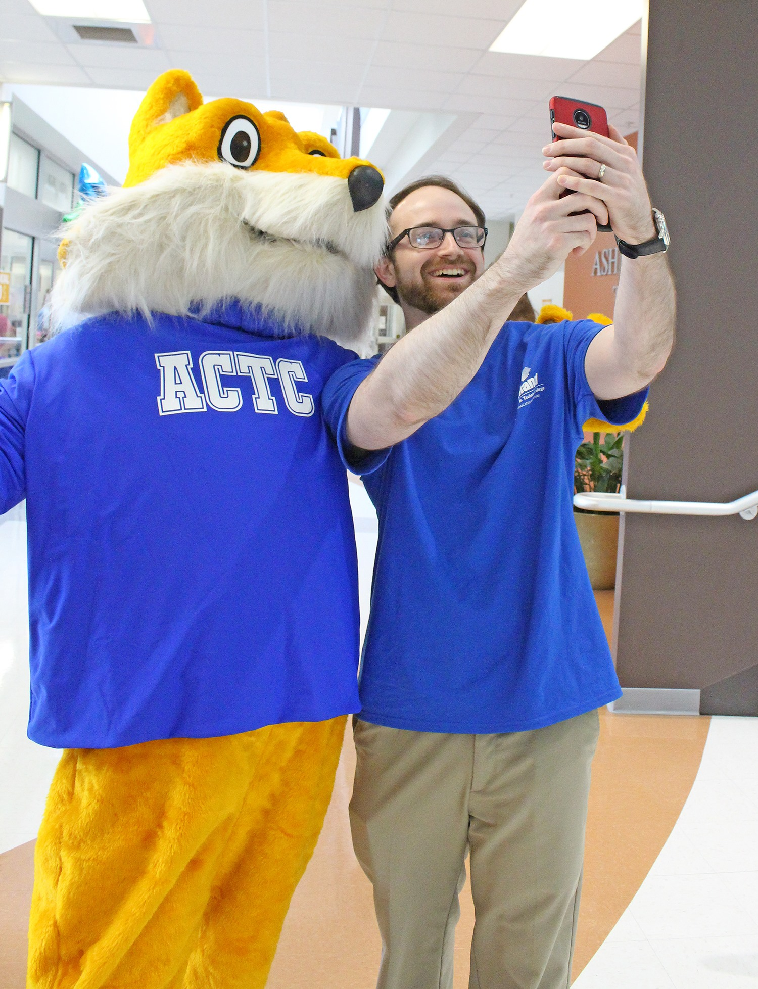 Ashland Community and Technical College staff posing for a selfie with the ACTC Pathfinder, the college's mascot
