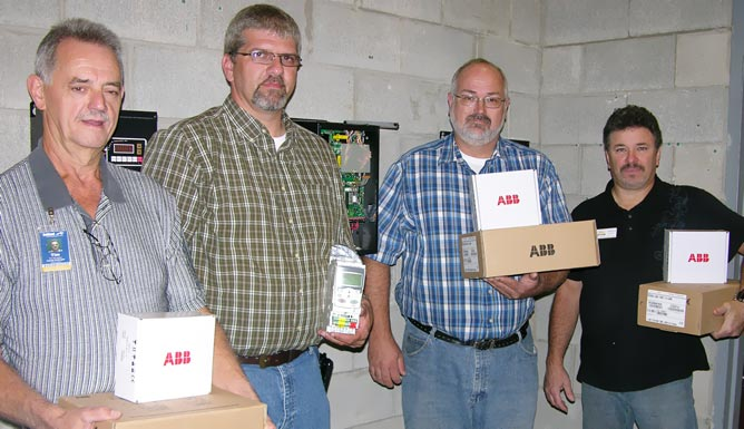 ACTC faculty and representtives from ABB Inc. hold some of the equipment donated to the school by ABB Inc.
