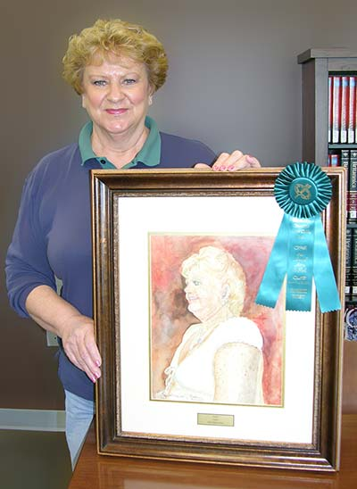 Janet displays her painting and ribbon.