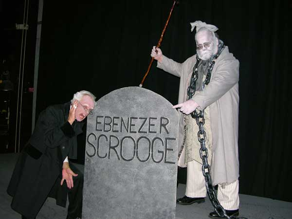 Marley's Ghost shows Scrooge his tombstone.